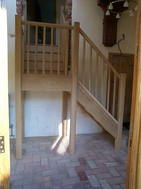 Oak stairs with half landing, stop chamfered newels and spindles. Closed riser and bull nose bottom tread