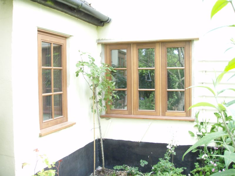 Single and triple casement stained timber windows with double horizontal bars